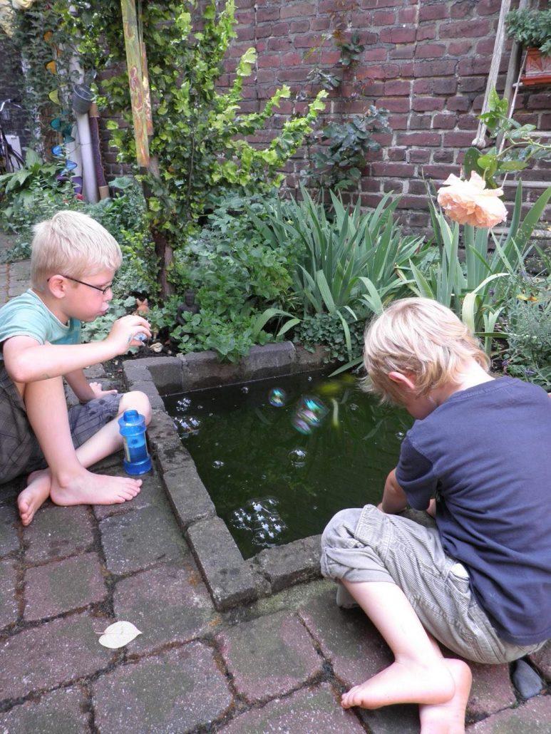 Zwei Kinder spielen mit Seifenblasen